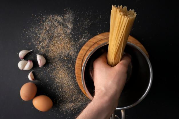Draufsicht von rohen harten spaghettis in einem metalltopf, kochendes wasser, bestandteile für herum kochen Premium Fotos