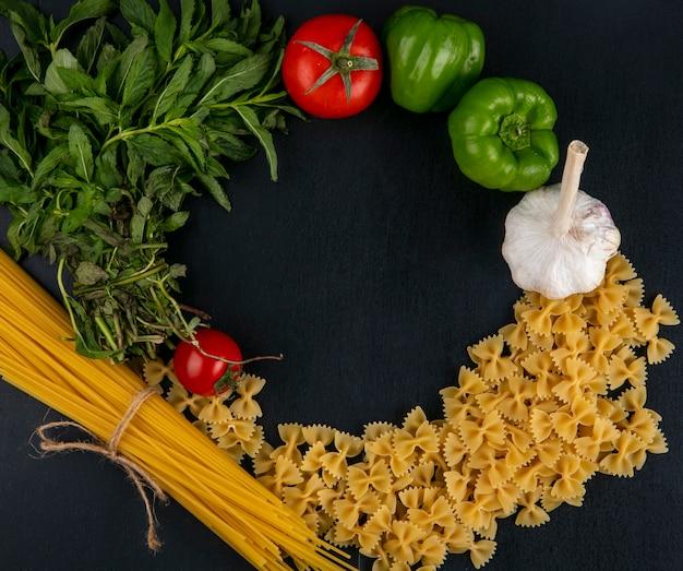 Draufsicht von rohen nudeln mit spaghettitomaten knoblauch und paprika mit minze auf einer schwarzen oberfläche Kostenlose Fotos
