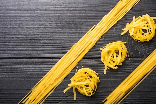 Draufsicht von rohen spaghettis zwischen den bandnudeln auf schwarzem hölzernem hintergrund Kostenlose Fotos