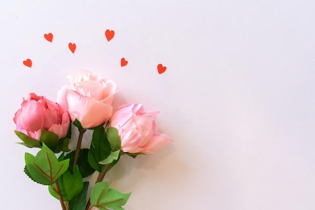 Draufsicht von rosen und von herzen formen auf rosa farbhintergrund für valentinstag- und muttertagkonzept Premium Fotos