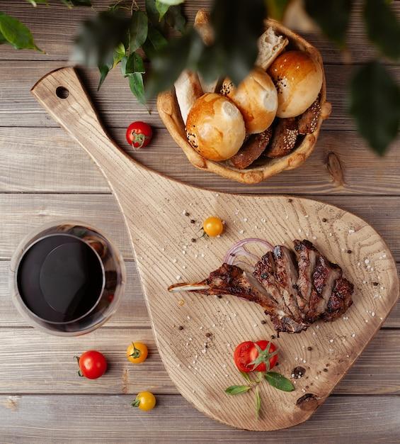 Draufsicht von steakscheiben auf knochen mit meersalz besprüht, kirschtomate Kostenlose Fotos
