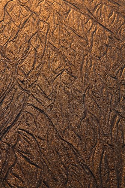 Draufsicht von strukturierten linien hintergrund auf sand im strand geschaffen durch die ebbe. Premium Fotos