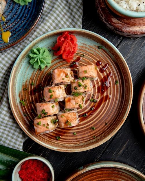 Draufsicht von sushi-rollen mit lachs eingelegten ingwerscheiben und wasabi auf einem teller auf rustikalem Kostenlose Fotos