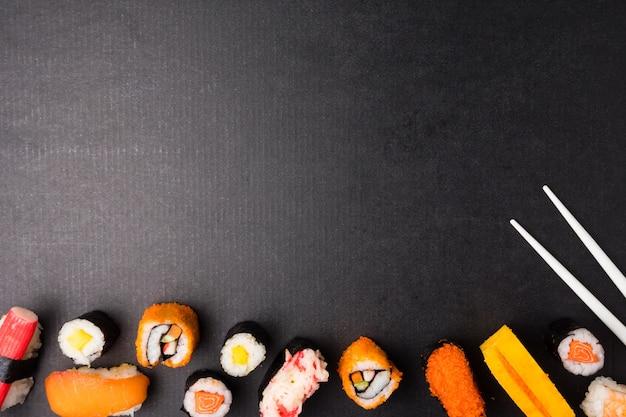 Draufsicht von sushi stellte und essstäbchen auf schwarzem hintergrund, japanisches lebensmittel ein. Premium Fotos