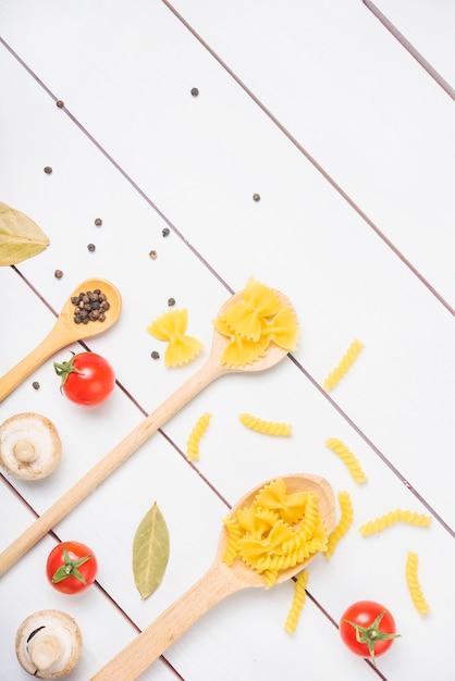 Draufsicht von teigwarenbestandteilen mit gewürzen und gemüse auf weißer plankentabelle Kostenlose Fotos
