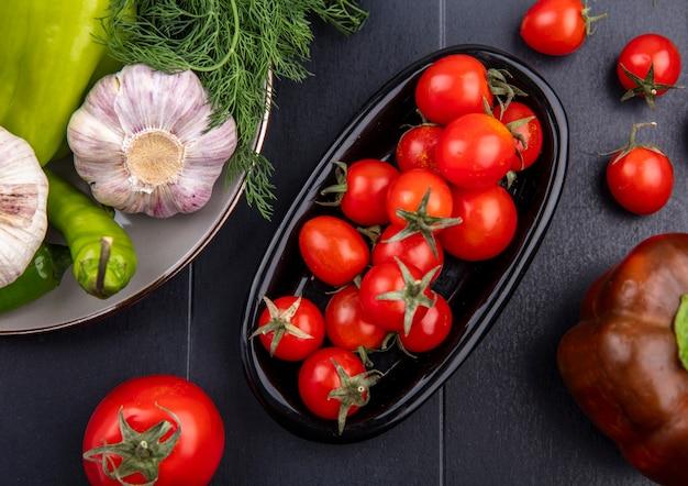 Draufsicht von tomaten in platte und platte von dillknoblauchpfeffer auf schwarzer oberfläche Kostenlose Fotos