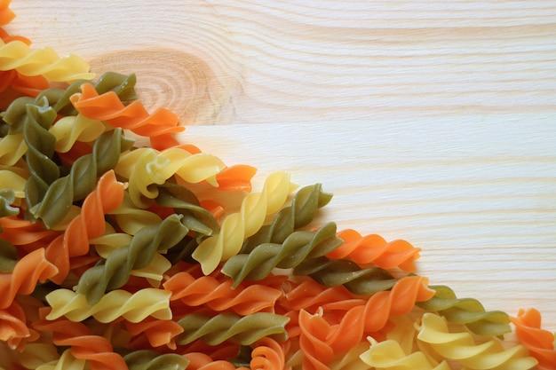 Draufsicht von ungekochten dreifarbenspirale formte teigwaren auf holztisch Premium Fotos