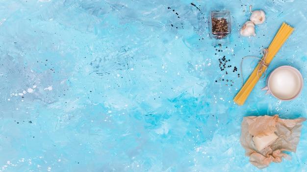 Draufsicht von ungekochten spaghettiteigwaren und -bestandteil auf blauem hintergrund Kostenlose Fotos