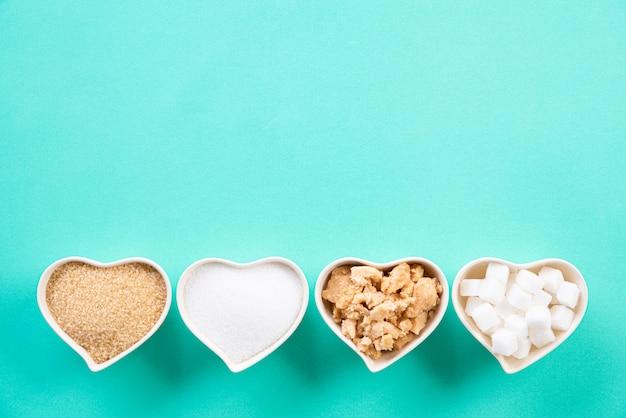 Draufsicht von verschiedenen arten des zuckers auf grünem pastell. Premium Fotos