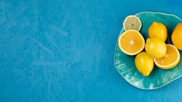 Draufsicht von zitronen in der platte mit blauem hintergrund Kostenlose Fotos
