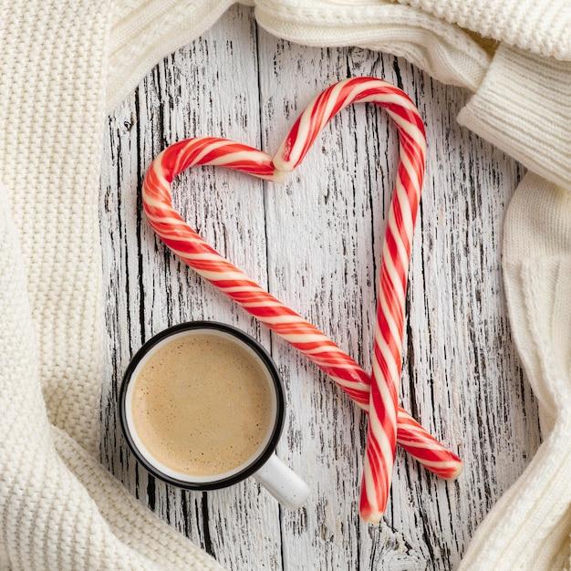Draufsicht von zuckerstangen in herzform mit tasse heißem kakao Kostenlose Fotos