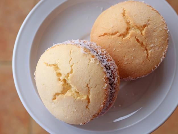 Draufsicht von zwei alfajores, traditionelle lateinamerikanische bonbons diente auf einer weißen platte Premium Fotos