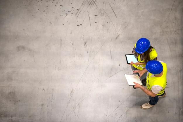Draufsicht von zwei industriearbeitern, die schutzhelme und reflektierende jacken tragen, die tablette und checkliste auf grauem betonboden halten Kostenlose Fotos
