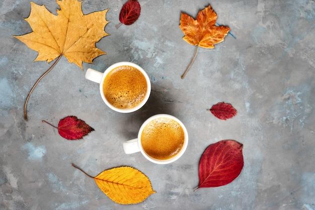 Draufsicht von zwei tassen kaffee um gelbe blätter Premium Fotos