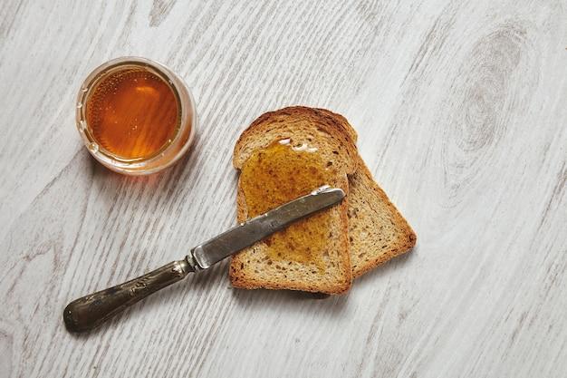 Draufsicht von zwei toast vom organischen rustikalen trockenen roggenbrot mit handwerklichem honig lokalisiert auf gealtertem gebürstetem weißem holztisch und weinlesemesser auf croutons Kostenlose Fotos
