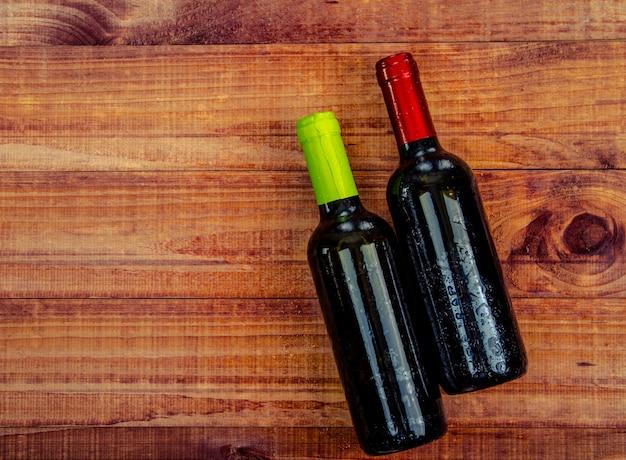Draufsicht von zwei weinflaschen auf einer rustikalen hölzernen tabelle Premium Fotos
