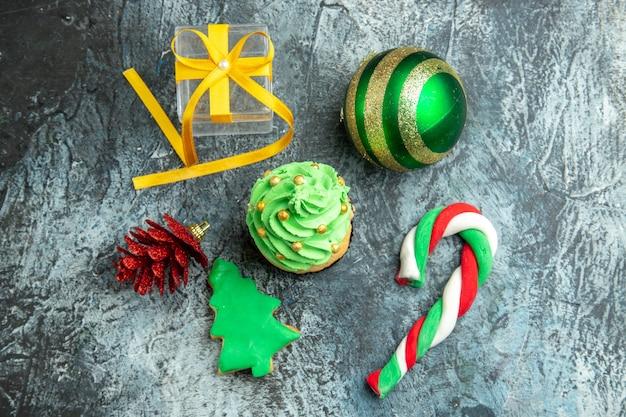 Draufsicht weihnachtsbaum cupcake weihnachtsbonbons weihnachtsbaumspielzeug auf grauer oberfläche Kostenlose Fotos