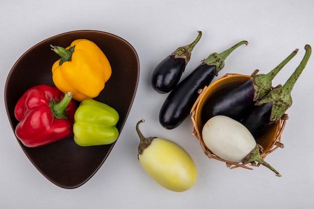 Draufsicht weiße und schwarze auberginen in einem korb mit farbigem paprika in einer schüssel auf weißem hintergrund Kostenlose Fotos