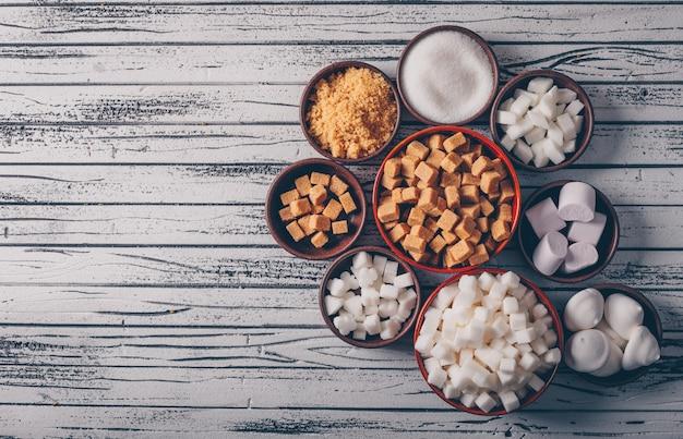 Draufsicht weißer und brauner zucker mit marshmallow in schalen auf hellem holztisch. Kostenlose Fotos