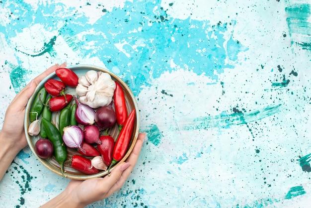 Draufsicht zwiebeln und knoblauch mit roten kühlen paprikaschoten innerhalb der runden platte auf dem hellblauen hintergrundbestandteilproduktlebensmittelmahlzeitgemüse Kostenlose Fotos