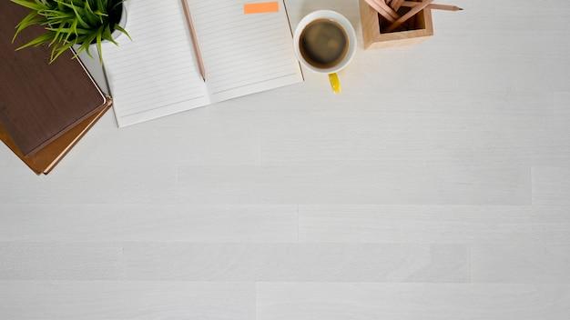 Draufsichtarbeitsplatz mit buch, notizbuch, bleistift und kaffee auf weißer hölzerner tabelle. Premium Fotos