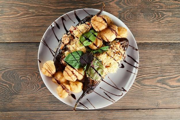 Draufsichtaufnahme eines tellers voller gebratener käsebällchen, serviert mit auberginen und bazam-balsamico-essig-sauce restaurant cafe kochen kulinarische küche delikatesse appetit lecker. Kostenlose Fotos