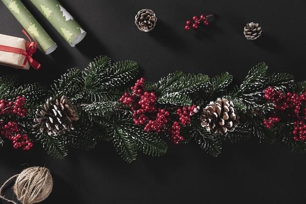 Draufsichtaufnahme von tannenzweigen mit kegel und geschenk auf einem schwarzen hintergrund Kostenlose Fotos