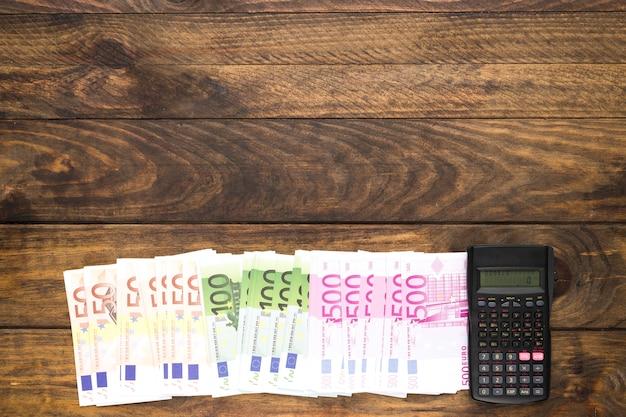 Draufsichtbanknoten und -taschenrechner auf hölzernem hintergrund Kostenlose Fotos