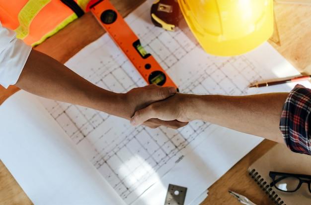Draufsichtbauarbeiter-teamauftragnehmer-handerschütterung Premium Fotos
