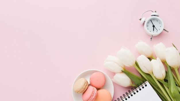 Draufsichtblumenstrauß von tulpenblumen mit bonbons und uhr Kostenlose Fotos