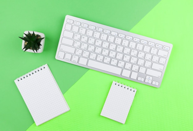 Draufsichtbriefpapieranordnung auf grünem hintergrund mit leeren notizblöcken Kostenlose Fotos