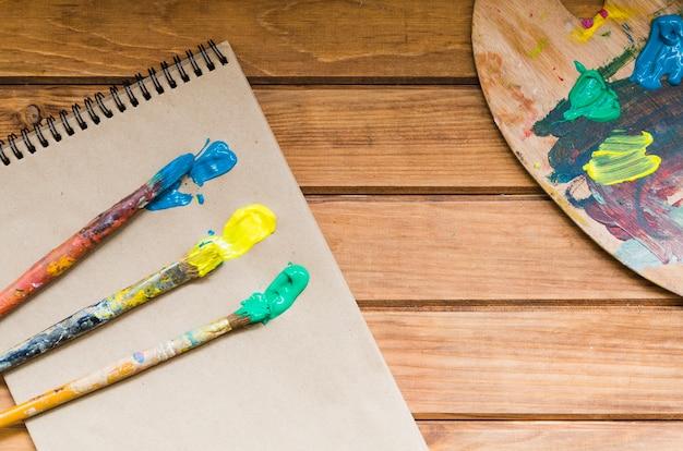 Draufsichtbürsten mit farbe auf notizbuch Kostenlose Fotos