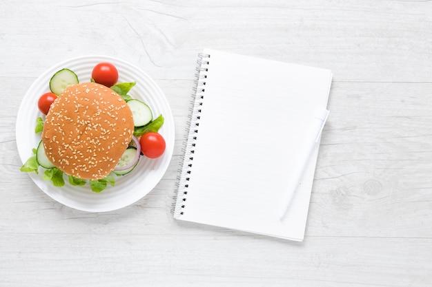 Draufsichtburger für veganer nahe bei leerem notizbuch Kostenlose Fotos