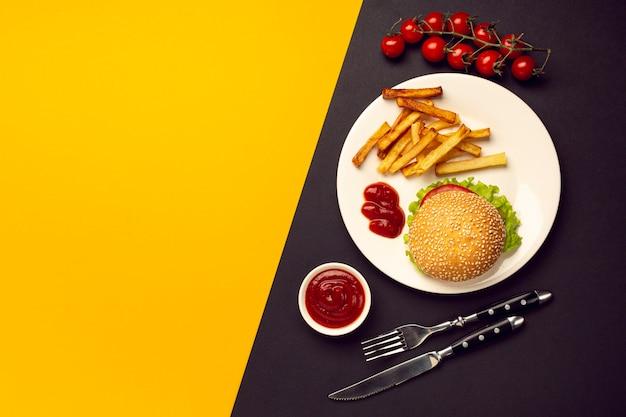 Draufsichtburger mit pommes-frites auf einer platte Kostenlose Fotos