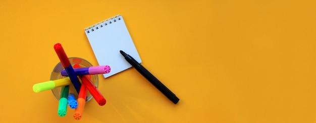Draufsichtfahne von filzstiften und von leerem notizblock auf gelb Premium Fotos