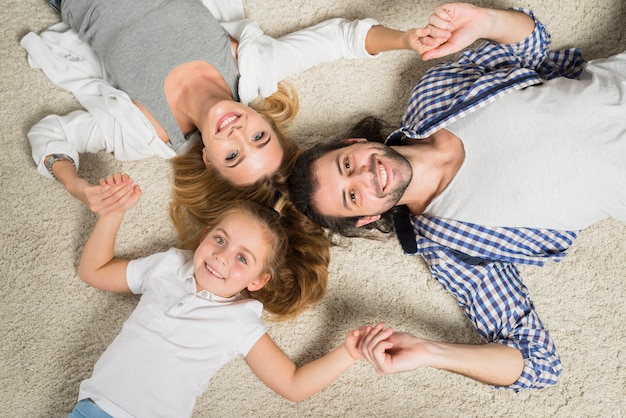 Draufsichtfamilienporträt, das auf teppich legt Kostenlose Fotos