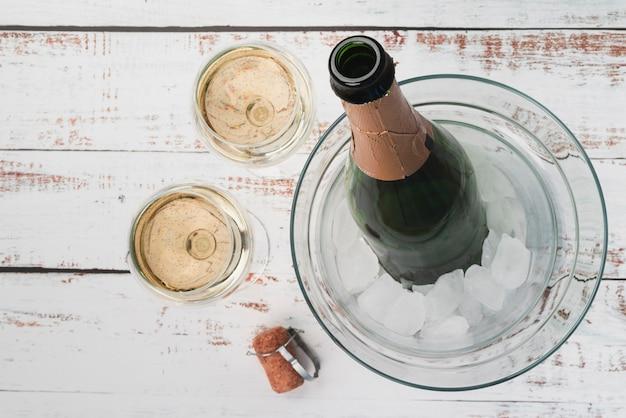 Draufsichtflasche mit champagnergläsern Kostenlose Fotos