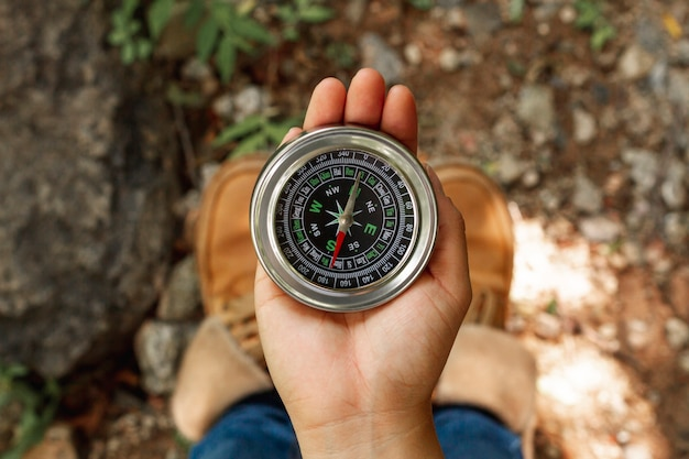 Draufsichtfrau, die kompass für richtungen verwendet Kostenlose Fotos