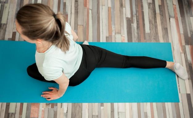 Draufsichtfrau, die yoga zu hause praktiziert Kostenlose Fotos