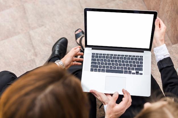 Draufsichtfrau und -mann, die laptop halten Kostenlose Fotos