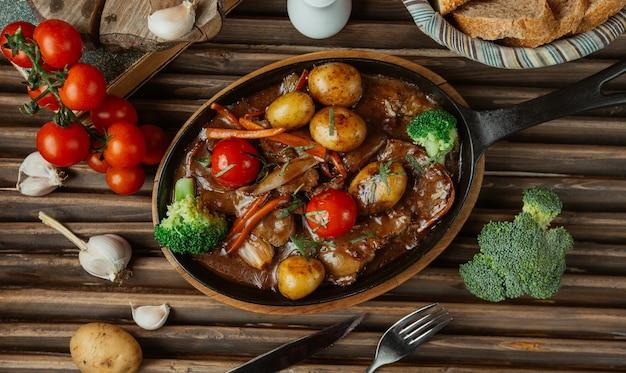 Draufsichtgemüserindfleischeintopfgericht in einer tonwarenwanne. Kostenlose Fotos