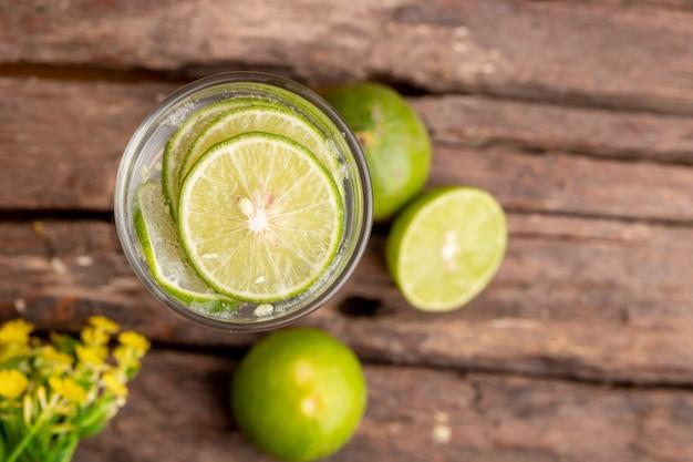 Draufsichtgrünkalk geschnitten im sodawasser- und glasplatz auf dem holztisch mit gelben blumen Premium Fotos