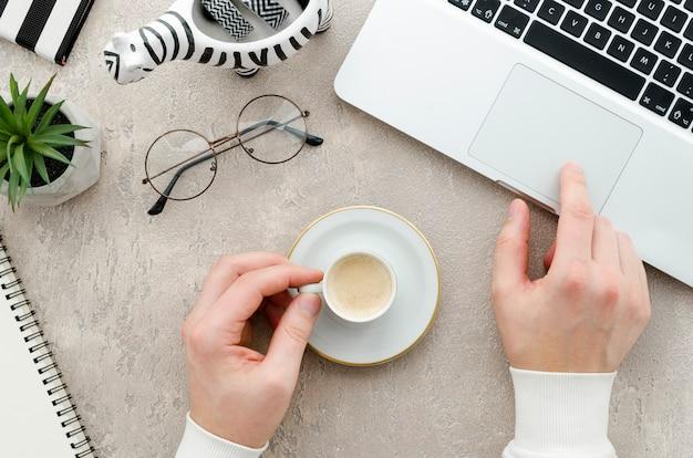 Draufsichthände mit kaffee und laptop Kostenlose Fotos