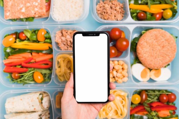 Draufsichthand, die leeres telefon über verschiedene lunchboxen hält Kostenlose Fotos