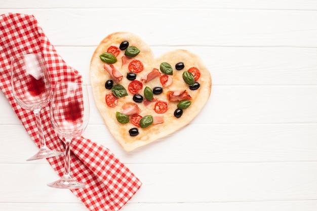 Draufsichtherz formte pizza auf tabelle mit stoff Kostenlose Fotos