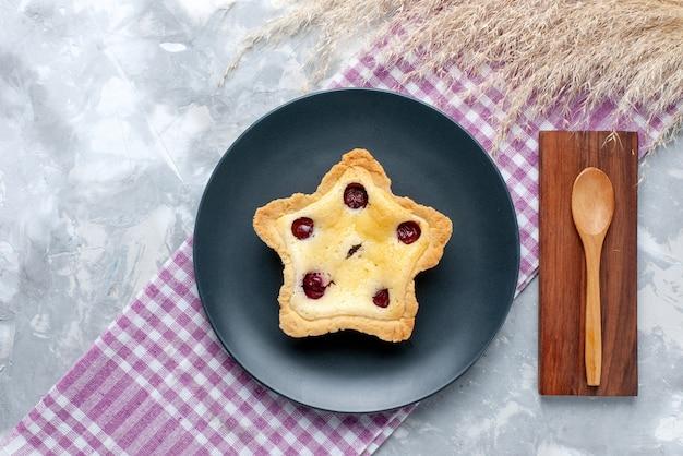 Draufsichtiger sternförmiger kuchen mit kirschen innen auf dem süßen zuckertee-auflaufkuchen des hellen tischkuchens Kostenlose Fotos