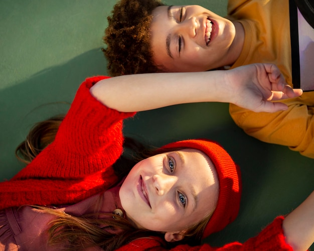 Draufsichtkinder, die zusammen auf einem basketballfeld liegen Kostenlose Fotos