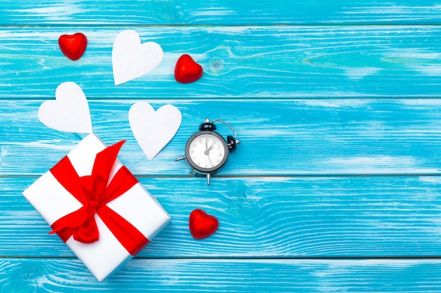 Draufsichtliebesfeiertagsfeier kreative valentine day-romantische zusammensetzungsebenenlage roter herzkalender-datumsblauer hölzerner hintergrund Premium Fotos