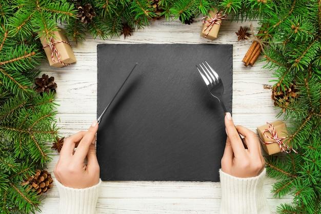 Draufsichtmädchen hält gabel und messer in der hand und ist essfertig. leere schwarze schieferquadratplatte. feiertagsabendessentellerkonzept mit dekor des neuen jahres Premium Fotos