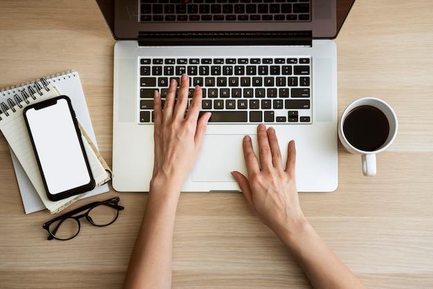 Draufsichtmann, der auf laptop schreibt Kostenlose Fotos